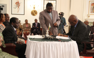 OLD GUARD: Finance Minister Patrick Chinamasa signs his letter of appointment as President Robert Mugabe looks on. Mr Chinamasa is largely credited for introducing the US dollar and the rand as the currencies of choice in his first short stint as finance minister in 2008-09. He was also the justice minister in the unity government.